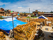 04 AUGUST 2015 - BUNGAMATI, NEPAL: Bricks stacked up around the site of the Hindu temple in Bungamati, a village about an hour from Kathmandu. The temple was destroyed in the earthquake and the plaza around the temple has been turned into an Internal Displaced Person (IDP) camp. Three months after the earthquake debris from the earthquake still clogs many of the streets in the community. The Nepal Earthquake on April 25, 2015, (also known as the Gorkha earthquake) killed more than 9,000 people and injured more than 23,000. It had a magnitude of 7.8. The epicenter was east of the district of Lamjung, and its hypocenter was at a depth of approximately 15 km (9.3 mi). It was the worst natural disaster to strike Nepal since the 1934 Nepal–Bihar earthquake. The earthquake triggered an avalanche on Mount Everest, killing at least 19. The earthquake also set off an avalanche in the Langtang valley, where 250 people were reported missing. Hundreds of thousands of people were made homeless with entire villages flattened across many districts of the country. Centuries-old buildings were destroyed at UNESCO World Heritage sites in the Kathmandu Valley, including some at the Kathmandu Durbar Square, the Patan Durbar Squar, the Bhaktapur Durbar Square, the Changu Narayan Temple and the Swayambhunath Stupa. Geophysicists and other experts had warned for decades that Nepal was vulnerable to a deadly earthquake, particularly because of its geology, urbanization, and architecture.    PHOTO BY JACK KURTZ