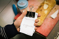 NAPLES, ITALY - APRIL 10th 2018: A waiter hold an order of pennette with Genovese sauce in the kitchen of the Trattoria Malinconico, a popular restaurant in the Vomero district in Naples, Italy, on April 10th 2018.<br /> <br /> Trattoria Malinconico was opened in 1953 by current owner Marianna Sorrentino's parents-in-law. At first it was only a bulk wine cellar, but then he began making a few cooked dishes – small plates that were popular with locals, which eventually morphed into larger meals. Still today the trattoria is frequented the neighborhood's older residents, many of whom have been loyal regulars for years, as well as younger locals and workers, who often stop by for a glass of wine. The menu varies from day to day, and is typically based on traditional Neapolitan recipes. Though some dishes, like meatballs, sausages, and friarielli (rapini, a type of broccoli typical to Naples), are always available.<br />  <br /> <br /> Genovese sauce is a rich, onion-based pasta sauce from the region of Campania, Italy. Likely introduced to Naples from the northern Italian city of Genoa during the Renaissance, it has since become famous in Campania and forgotten elsewhere.<br /> Genovese sauce is prepared by sautéing either beef, veal or pork in a large number of onions, for at least two but as many as ten hours. Large, cylindrical pasta like rigatoni, ziti or candele are favored because they can hold the rich sauce.