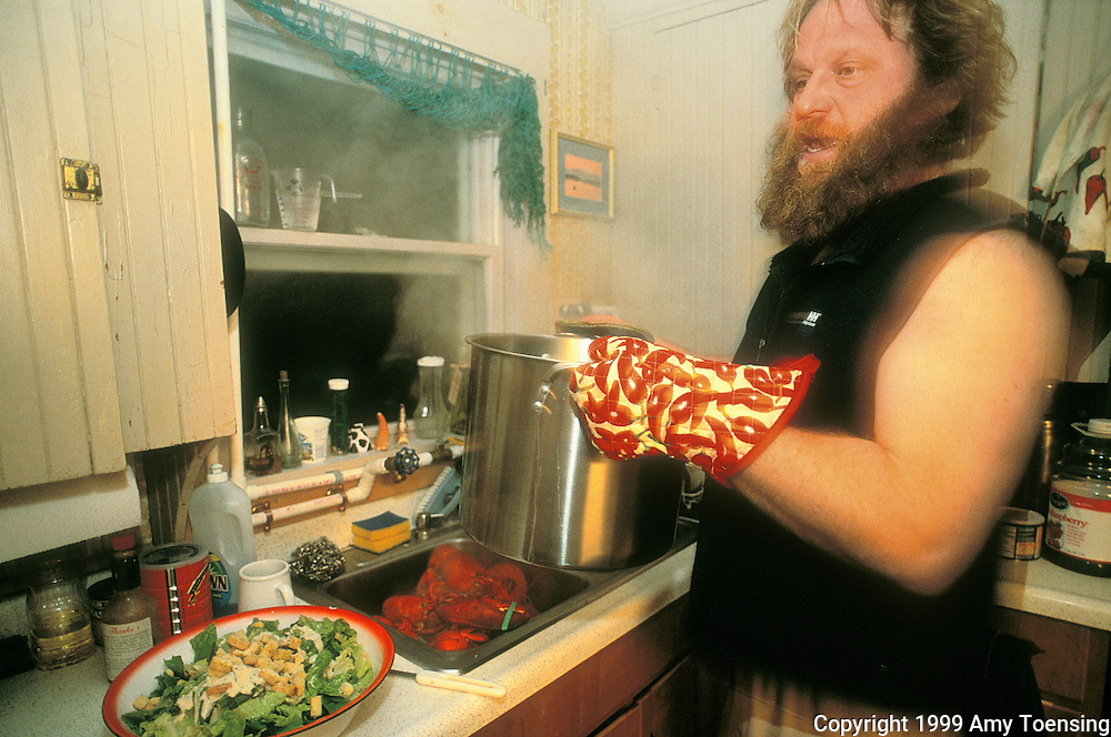 MONHEGAN ISLAND, MAINE - DECEMBER 04: Lobsterman Mattie Thomson cooks a lobster dinner for members of his crew, December 4, 1999 on Monhegan Island, Maine. Monhegan Island, home to lobstermen and painters and a popular destination for tourists is twelve miles off the coast of Maine. Ringed by high, dark cliffs, its interior a mix of meadows, marsh and spruce groves, Monhegan is one of just 14 true island communities left off the coast of Maine. The island has a 65 permanent, year-round residents and the population grows to around 200 in the summer, with day-trippers adding several hundred more. (Photo by Amy Toensing) _________________________________________<br /> <br /> For stock or print inquires, please email us at studio@moyer-toensing.com.