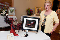 "Annette Hutchins sports a humorous interpretation of photo ""Life is Short...enjoy the ride"" along with her floral arrangement during the 6th annual Art 'N Bloom with Opechee Garden Club at Gilford Public Library Thursday evening.  (Karen Bobotas/for the Laconia Daily Sun)"