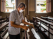 14 SEPTEMBER 2016 - BANGKOK, THAILAND: A volunteer cleans the interior of Santa Cruz church in Bangkok. Santa Cruz is one of the first Catholic churches in Bangkok. It was established by Portuguese mercenaries serving King Taksin the Great in 1770.         PHOTO BY JACK KURTZ