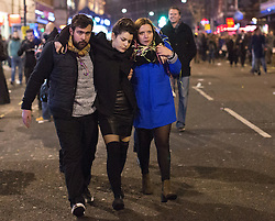 © Licensed to London News Pictures. 01/01/2015. Two friends carry their friend after a night out in central London to celebrate New Years Day. Photo credit : Isabel Infantes / LNP