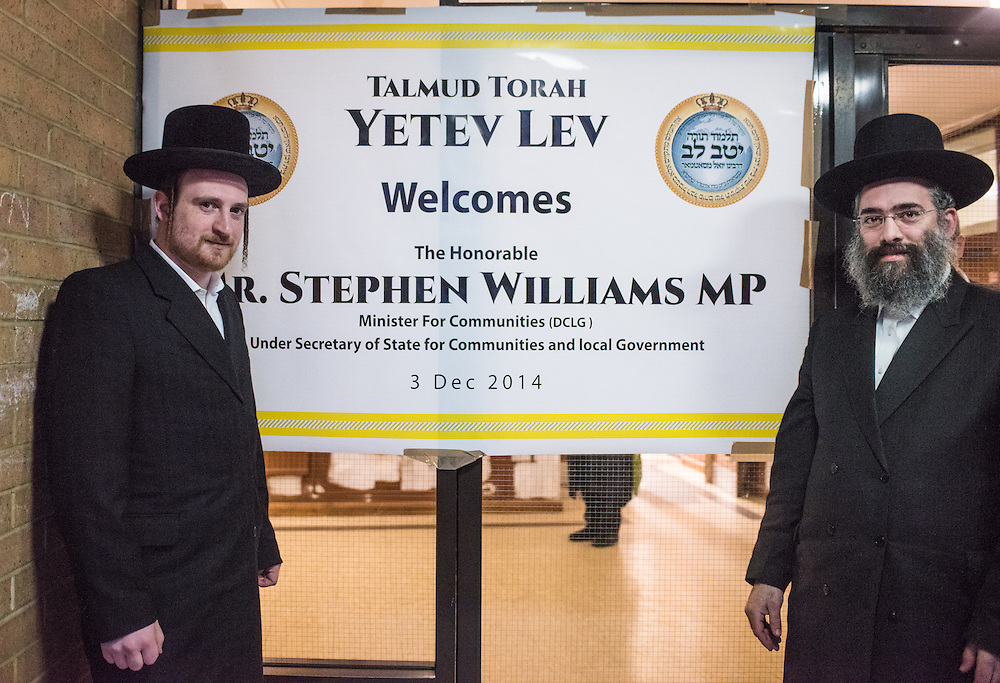 London, UK - 3 December 2014: members of the orthodox Jewish community pose next to a welcoming banner  as Mr Stephen Williams MP, Parliamentary Under Secretary of State for Communities and Local Government, visits Talmud-Torah Yetev-Lev orthodox Jewish school in Hackney, London