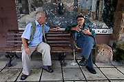 Konstandinos Delios (69) (L) pensioner and a supporter of the socialist party PASOK (in government), arguing about politics with a pensioner friend (R) who supports the communist party. They often meet on this bench outside the workers' union office, to enjoy their intense conversations. ..Mr Delios'  son who is a veterinarian is trying to find a way to emigrate outside Greece because after he lost his job he has difficulties finding a new one. His son is one of many young people who cannot find employment in Greece and because of that they emigrate. He supports his son as much as he can with the pension money he receives every month and he says that most families in once prospering Naousa are now surviving because of pensioners' money and whatever is left of their savings as the unemployment is very high...His pensioner friend who used to be a farmer, wary of the media declined to offer his name. He accused globalization for the current bad condition of Naousa city because it brought to Greece cheap products from China resulting in closing down Greek businesses.