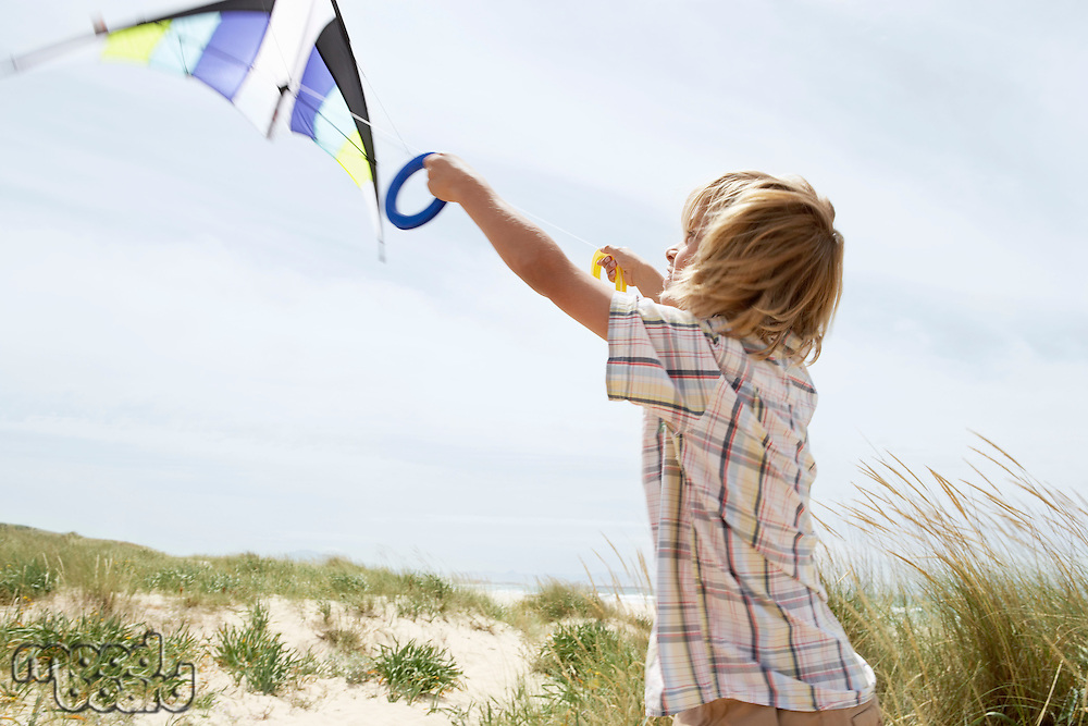 Pre-teen boy arms raised flying kite on windy beach side view
