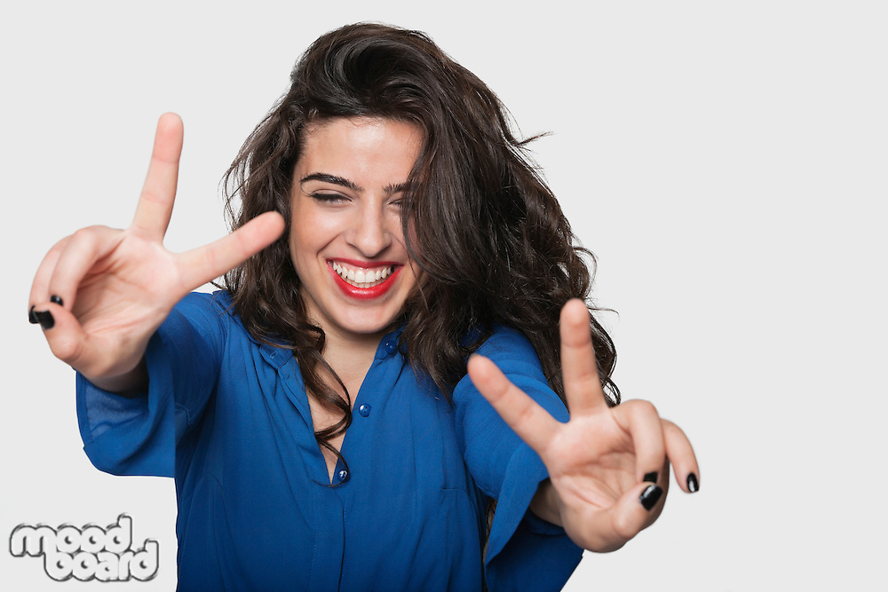 Happy young woman gesturing victory sign against gray background