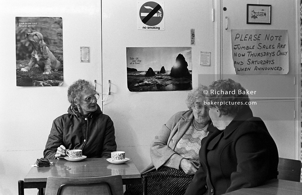 Beneath Christian posters, three elderly ladies pass the time of day at the Salvation Army's drop-in centre in Newport, Wales
