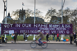 Westminster, London, December 2nd 2015.  As Parliament prepares to vote on air strikes on Islamic State terrorists in Syria, Stop The War and other groups opposed to British military involvement protest outside Parliament. PICTURED: Protesters have unfurled a giant banner in Parliament Square. ///FOR LICENCING CONTACT: paul@pauldaveycreative.co.uk TEL:+44 (0) 7966 016 296 or +44 (0) 20 8969 6875. ©2015 Paul R Davey. All rights reserved.