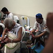 "THE PHILIPPINES (Manila). 2009. ""Cock doctors' clean and stitch up the wounded and injured winning birds who survive the fight to the death of two game cocks, each with three inch razor sharp blades fastened to their left ankles at the Makati, Makati City, Manila. Photo Tim Clayton <br /> <br /> Cockfighting, or Sabong as it is know in the Philippines is big business, a multi billion dollar industry, overshadowing Basketball as the number one sport in the country. It is estimated over 5 million Roosters will fight in the smalltime pits and full-blown arenas in a calendar year. TV stations are devoted to the sport where fights can be seen every night of the week while The Philippine economy benefits by more than $1 billion a year from breeding farms employment, selling feed and drugs and of course betting on the fights...As one of the worlds oldest spectator sports dating back 6000 years in Persia (now Iran) and first mentioned in fourth century Greek Texts. It is still practiced in many countries today, particularly in south and Central America and parts of Asia. Cockfighting is now illegal in the USA after Louisiana becoming the final state to outlaw cockfighting in August this year. This has led to an influx of American breeders into the Philippines with these breeders supplying most of the best fighting cocks, with prices for quality blood lines selling from PHP 8000 pesos (US $160) to as high as PHP 120,000 Pesos (US $2400).."