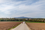Children cycling on a field road with view to the Taunus mountain in the back. The Taunus is a mountain range in Hessen, Germany, located north of Frankfurt.