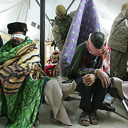4 December 2004..Mahmudiya, Iraq..Detainees in US custody.......US Marines launched a nightime raid (4 December) from a Forward Operating Base in the North Babel province of Iraq against the homes of suspected insurgents. The homes are searched for evidence and the detainees are transported to the Marine base, there blindfolded and with hands secured by strips of plastic (flexi-cuffs) they join detainees from previous raids. The prisoners are given blankets to fight the bitter cold and one at a time are led into a cubicle to be fingerprinted and photographed prior to further questioning.