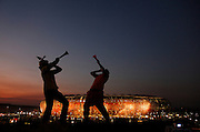 Silhouette of Football fans wearing a makarapa and blowing a vuvuzela with soccer city stadium with lights on at night in the background. Brazil V Ivory Coast. World cup group match. Soccer city. Johannesburg. South Africa.