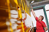 Levi Workman, with Twin Lakes Body & Frame, reaches for the top of the windows on a 1980 school bus while apply a clear coat Wednesday in Twin Lakes.