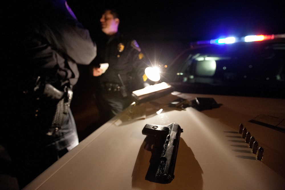 A 9mm handgun lies on the hood of a patrol car after being confiscated during a traffic stop. Dec. 9, 2011. Oxnard, Calif. (Photo by Gabriel Romero ©2011)