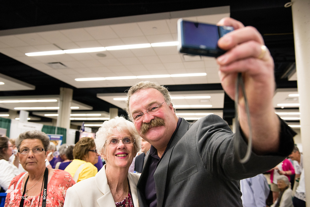 "The Rev. Dr. Matthew C. Harrison, president of The Lutheran Church–Missouri Synod, takes a ""selfie"" with Carol Ann Sander in the exhibit hall of the 36th Biennial Convention of the Lutheran Women's Missionary League on Friday, June 26, 2015, at the Iowa Events Center in Des Moines, Iowa. LCMS Communications/Erik M. Lunsford"