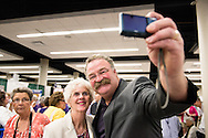"""The Rev. Dr. Matthew C. Harrison, president of The Lutheran Church–Missouri Synod, takes a """"selfie"""" with Carol Ann Sander in the exhibit hall of the 36th Biennial Convention of the Lutheran Women's Missionary League on Friday, June 26, 2015, at the Iowa Events Center in Des Moines, Iowa. LCMS Communications/Erik M. Lunsford"""