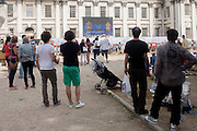 Spectators watch live TV coverage of the Diving event with Team GB athletes Tom Daley and Pete Waterfield at the old Royal Naval College, Greenwich on day 4 of the London 2012 Olympic Games. Greenwich Park is hosting the Olympic Equestrian competitions, plus the combined running and shooting event of the Modern Pentathlon. The Old Royal Naval College is the architectural centrepiece of Maritime Greenwich, a World Heritage Site in Greenwich, London. The buildings were originally constructed to serve as the Royal Hospital for Seamen at Greenwich, now generally known as Greenwich Hospital, which was designed by Christopher Wren, and built between 1696 and 1712.