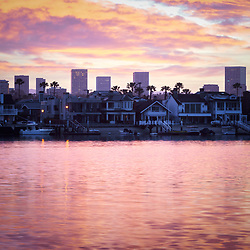 Newport Beach skyine sunrise photo with Balboa Island homes, Newport Harbor, and Fashion Island office buildings. Newport Beach is an affluent coastal city in Orange County Southern California. Photo is high resolution. Copyright ⓒ 2017 Paul Velgos with All Rights Reserved.