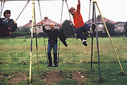 Teenagers on swings, Greenford, London, UK, 1980.