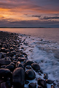 Dunstanburgh's pebble beach at sunset