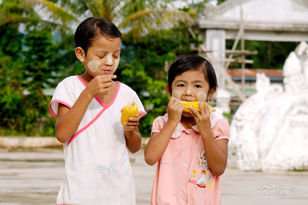 Two burmese girls eating corn