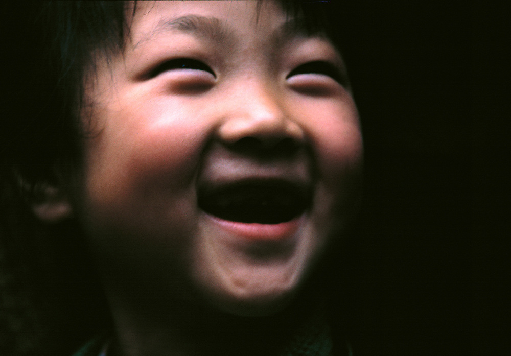 A young girl's smile lights up the dark, in Suzhou, China.