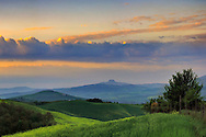 The sky started to clear off right at sunrise, after a night of mighty thunderstorms. Taken in the hills between  Pienza and San Quirico d'Orcia in Tuscany, Italy, on a morning at the beginning of May. The medieval fortified town of Radicofani is in the background.