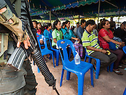26 OCTOBER 2016 - MYAWADDY, KAYIN STATE, MYANMAR: Soldiers from the Democratic Karen Buddhist Army - Border Guard Force, a pro-government militia made up of former anti-government guerillas, watch Myanmar refugees repatriated to Myanmar from Thailand. Sixtyfive Burmese refugees living in the Nupo Temporary Shelter refugee camp in Tak Province of Thailand were voluntarily repatriated to Myanmar. About 11,000 people live in the camp. The repatriation was the first large scale repatriation of Myanmar refugees living in Thailand. Government officials on both sides of the Thai / Myanmar border said the repatriation was made possible by recent democratic reforms in Myanmar. There are approximately 150,000 Burmese refugees living in camps along the Thai / Myanmar border. The Thai government has expressed interest several times in the last two years in starting the process of repatriating the refugees.     PHOTO BY JACK KURTZ