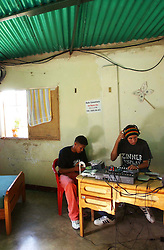 "Davis Semeco, righ, plays music  on ""A New Day Radio"", a community radio station in Caracas, as his friend Edgar Russian listens.  The station operates out of the home of  Zulay Zerpa,  who donates the space in her bedroom 7 days a week between 3pm and 9pm.   Chavez and his government have been increasingly supportive of these generally Chavista community media stations as a response to the anti-chavista private media."