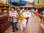 "29 SEPTEMBER 2012 - NAKORN NAYOK, THAILAND:  Thai Buddhists carry offerings to Ganesh during observances of Ganesh Ustav at Wat Utthayan Ganesh, a temple dedicated to Ganesh in Nakorn Nayok, about three hours from Bangkok. Many Thai Buddhists incorporate Hindu elements, including worship of Ganesh into their spiritual life. Ganesha Chaturthi also known as Vinayaka Chaturthi, is the Hindu festival celebrated on the day of the re-birth of Lord Ganesha, the son of Shiva and Parvati. The festival, also known as Ganeshotsav (""festival of Ganesha"") is observed in the Hindu calendar month of Bhaadrapada, starting on the the fourth day of the waxing moon. The festival lasts for 10 days, ending on the fourteenth day of the waxing moon. Outside India, it is celebrated widely in Nepal and by Hindus in the United States, Canada, Mauritius, Singapore, Thailand, Cambodia, Burma , Fiji and Trinidad & Tobago.     PHOTO BY JACK KURTZ"