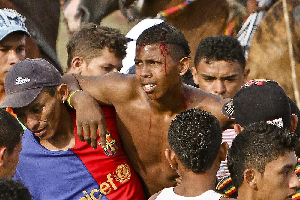 Un torero es asistido por sus compañeros después de ser embestido por un toro durante una corraleja en Since, Sucre, Colombia.