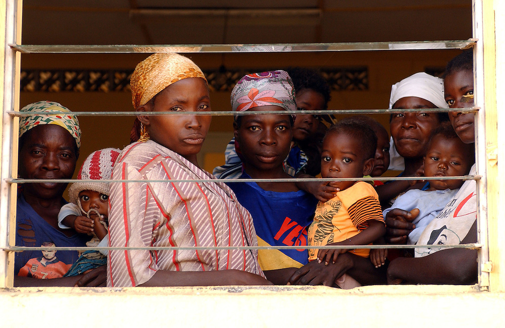 Anxious mothers and babies look out the window of a ward in Camacupa Hospital, Angola.