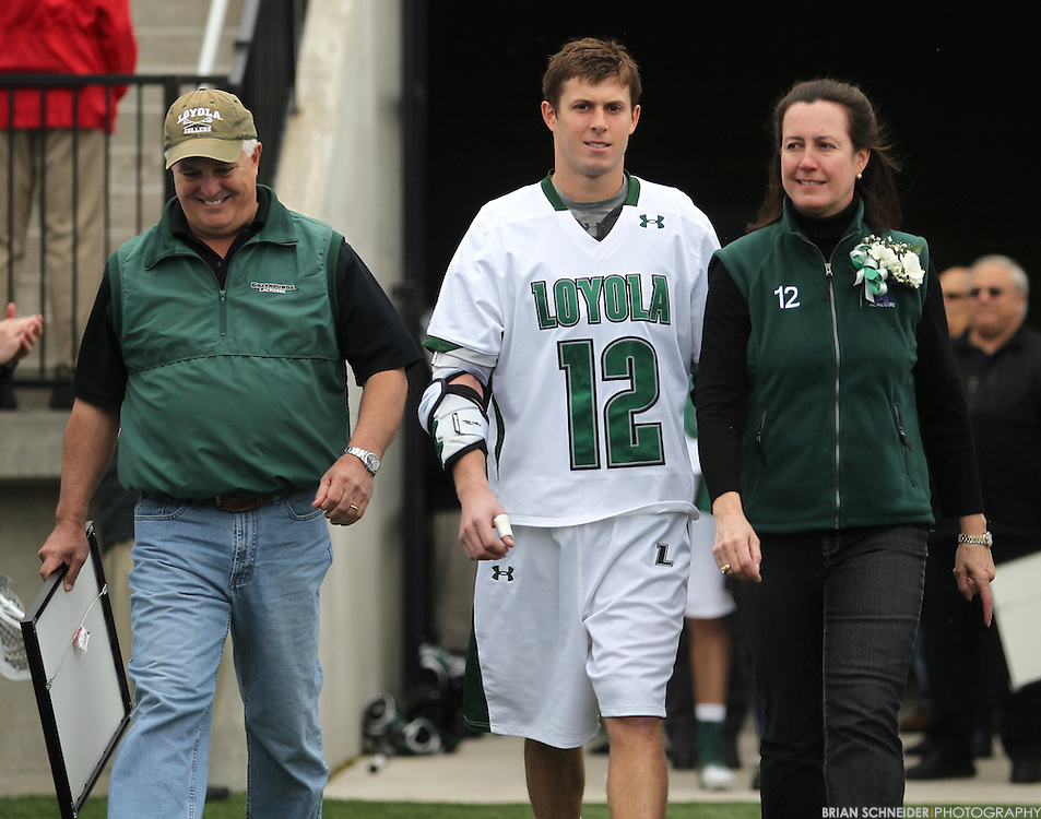 April 28, 2012; Baltimore, MD, USA; Loyola Greyhounds attack Eric Lusby (12) walks in with family before the game against the Johns Hopkins Blue Jays at  Ridley Athletic Complex in Baltimore, MD. Mandatory Credit: Brian Schneider-www.ebrianschneider.com