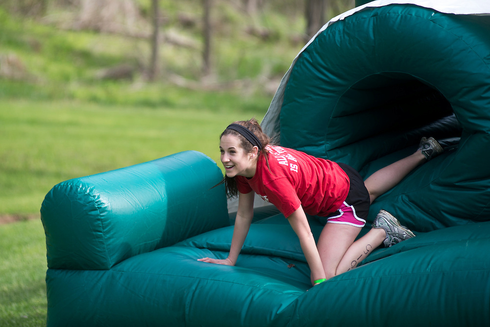 Emily Doyle crawls through the inflatable obstacle course during the first part of the O'Bleness Race for a Reason Mud Run, Saturday, April 27, 2013. The course included a four-mile run up to the old Army ROTC Course at the Ridges, through the Radar Hill Trail and back to Tail Great Park across from Peden Stadium. Race for a Reason, Race 4 A Reason, Annual Events, Events, Students, Faculty & Staff