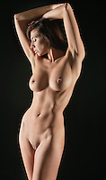 Front view of naked young woman with hands behind head over black background