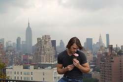 man smelling a rose on a rooftop overlooking New York City