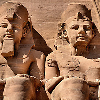 Pharaoh Ramesses II Statues at Temple of Ramesses in Abu Simbel, Egypt<br /> It is extremely hot in southern Egypt on the shores of Lake Nasser. Located there is the almost deserted town of Abu Simbel. Few people would visit here if not for two spectacular temples built by Ramesses II. He ruled for 66 years until he died in his mid-nineties in 1213 BC. These are two of four colossal statues of the pharaoh sculpted into the face of a cliff. They guard the entrance to the Great Temple. This is also called the Temple of Re-Harakhte or the Sun Temple. These magnificent carvings are over 65 feet tall. They portray him on his throne wearing a double crown and a nemes headdress. Notice on the left that his false beard is still intact.