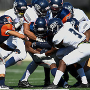 Fullerton College players tackle the Orange Coast College ball carrier in a game played on Saturday afternoon.