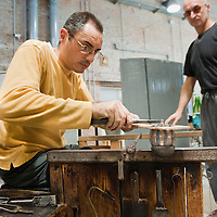 "VENICE, ITALY - DECEMBER 14:  Marino Santi, master ""maestro"" glass maker and assistant Stefano Costantini at Eugenio Ferri & C.  in Murano make glass Christmas baubles on December 14, 2010 in Venice, Italy. The production of glass baubles is an highly skilled process,with a variety of styles, often with the inclusion of gold and silver foil.  (Photo by Marco Secchi/Getty Images)"