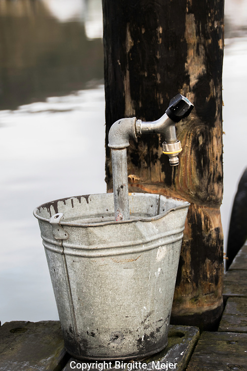 Zink bucket with waterpipe and water tap in front of a wooden pole, in the background the sea.