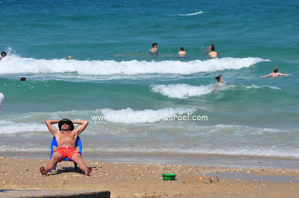 Israel, Haifa, Carmel Beach, Israelis go to the Beach on a warm, sunny  day. Man on chair sunbathing