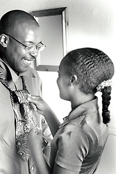 Girl helping her father with his tie. UK 1990s