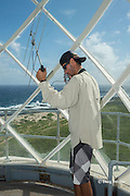 NOAA researcher Mark Sullivan uses a VHF radio receiver and antenna from top of Kalaupapa Lighthouse to try to locate a Hawaiian monk seal carrying a Crittercam and tracking instrumentation package attached a few days earlier by NOAA scientists, Kalaupapa Historical Park, Kalaupapa Peninsula, Molokai, Hawaii, USA