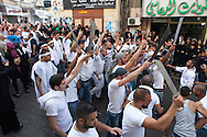 Procession of shiite muslim men, carrying traditional swords, during the Day of Ashura, Nabatieh, Lebanon (November 14, 2013).