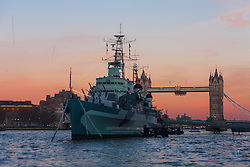 London, November 24th 2014. With London having enjoyed a clear if cold day, weather forecasters are predicying a cold night with temperatures expected to dip as low as 3 degrees in the early hours of Tuesday. PICTURED: HMS Belfast breaks the chilly post-sunset skyline, with Tower Bridge in the background.