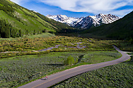 A bicyclist rides along Castle Creek Road in Ashcroft, Colorado.