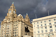 The Liver Building in the sun, with ominous clouds behind, along the shores of the River Mersey, Liverpool.