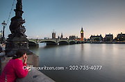 A woman looks across the River Thames at the Westminster Bridge, Big Ben and the Houses of Parliament in London, England.