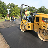 Murphee Paving employee J.P. Wates rolls a new layer of asphalt around the track at Robins Noble Park on Madison Street Wwednesday. The City of Tupelo is in the process of resurfacing the track at the park as years of neglect.