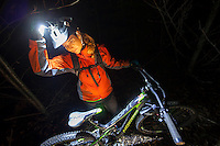 """A young adult woman adjusts her nightlight while riding """"Missing Link"""", one of Cumberland's well known mountain bike trails.  Cumberland, The Comox Valley, Vancouver Island, British Columbia, Canada."""